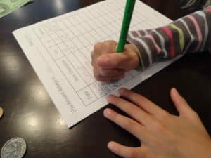 girl managing allowance with pencil and paper